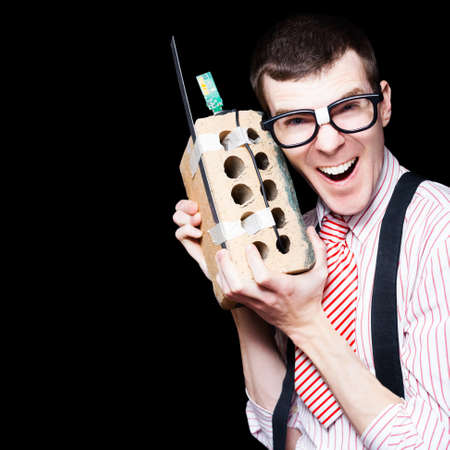 wireless telephone: Laughing Business Geek Talking On A Mobile House Brick Telephone In A Funny Depiction Of The Wireless Technology Evolution
