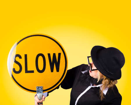 odd: Odd businessman looking at slow traffic sign during difficult working conditions on yellow background