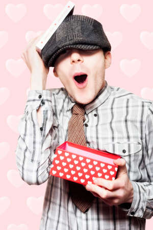 first day: Surprised School Boy Opening Valentines Day Present In A Romantic Depiction Of Love At First Sight On Pink Heart Background