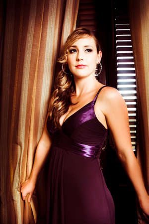 decolletage: Beautiful glamour model with curled hair standing indoors in front of a curtain in elegant dark purple evening dress with a plunging neckline Stock Photo