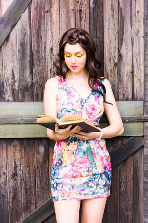 leisurely: Relaxed Pretty Young Brunette Woman Reading A Old Book Outdoors By A Old Rustic Wood Door In A Calm And Tranquil Leisurely From Of Entertainment Stock Photo