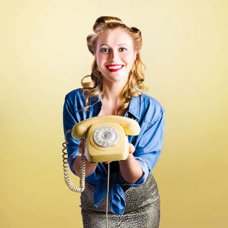 advertise with us: Adorable female pinup model holding olden day rotary phone in a call us now concept on yellow gradient background