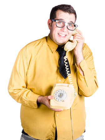 slicked: worried looking man on an old fashioned corded phone, taking important call