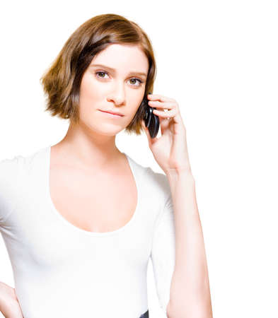 sales rep: Half Body Isolated Studio Portrait Of A Pretty And Young Brunette Business Woman With Short Hair Chatting And Communicating Sales Through A Mobile Phone Stock Photo