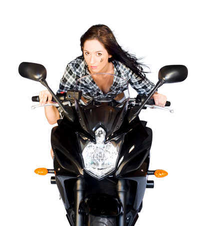 Beautiful woman crouched low over the handlebars of her motorbike head on to the camera as she satisfies her need for speed