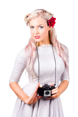 looking around: Attractive young blond woman with camera around neck, white background