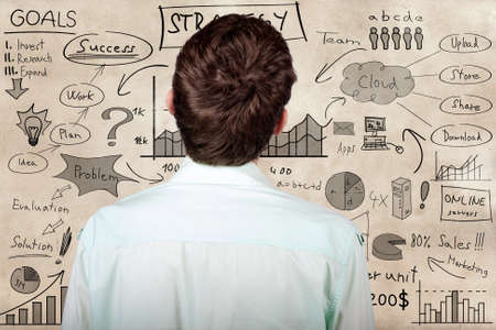 business process: Creative businessman looking to develop innovative business plan when looking to hand drawn marketing illustration on a texture wall
