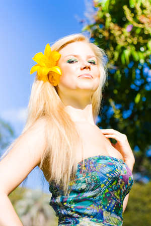 jaunty: Jaunty beautiful young woman wearing a bright yellow flower in her hair with her head held high, low angle portrait