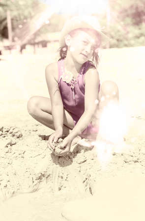 olden day: Artistically aged and faded vintage photo of a young girl in a hat playing in the sand on a beach in a grunge summer fun concept