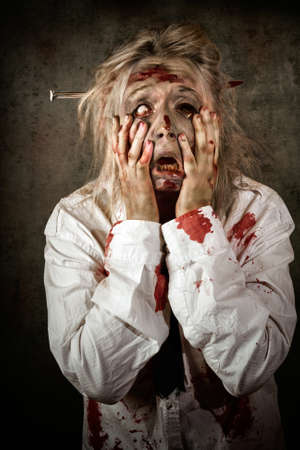 protruding eyes: Grunge portrait of a shocked bloody female business zombie with hands to decaying face and maggots crawling from eye-socket. Shock horror concept Stock Photo