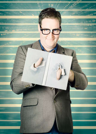 poking: Funny portrait of a male nerd holding book with fingers poking through plot hole twist. Bookworm Stock Photo