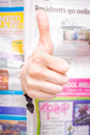 acceptable: In Breaking News A Hand With Thumbs Up Punches Through A Newspaper Article In A Symbol Of Good News Or Thumbs Up Review Indicating A Positive Press Write Up