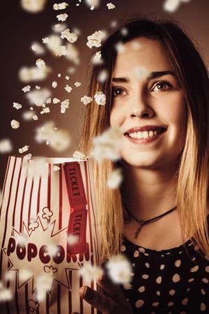 cinta pelicula: chica audiencias cine de época sonriendo al ver la película en una caída artístico creativo de palomitas de maíz. pase de películas