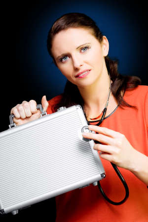 reconsideration: Closeup portrait of cute young business woman smiling while conducting a business review with stethoscope and briefcase on dark background