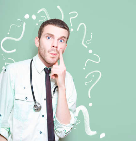 bewildered: Confused Healthcare Doctor Standing Looking Puzzled Against A Green Question Mark Background In A Depiction Of A Unknown Cure Or Medical Mystery Stock Photo