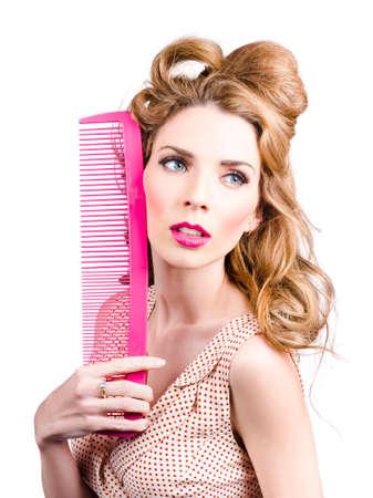 pin up model: Sensual female pin up model holding massive pink hair brush. Stylish hair care Stock Photo
