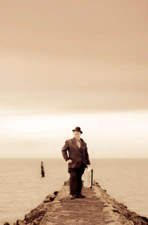 destinations: Old Faded Photograph Of A Senior Man Standing At His Final Destination When On The Journey Of A Life Time Stock Photo