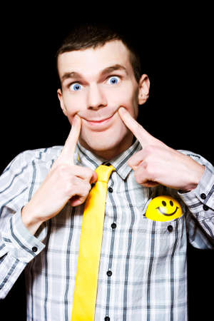 comedian: Smiling Young Man Comedian Putting On A Happy Face When Turning A Frown Upside Down, With Smile Ball In Pocket On Dark Black Copyspace Background