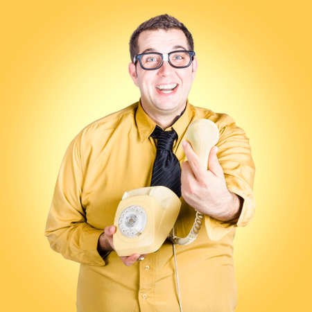 quirky: Humorous photo of a quirky business geek giving great news information when tendering over a old-fashion phone. Yellow studio background Stock Photo