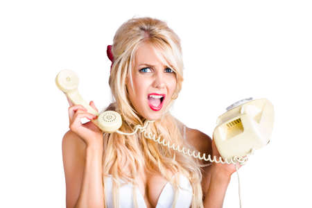 appalled: Confused young blond woman holding retro telephone, crossed wires concept on white background Stock Photo