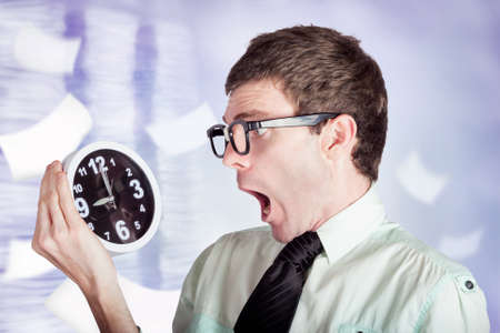 aghast: Overloaded businessman standing in a modern office flooded with paper work holding over time clock with look of stress Stock Photo