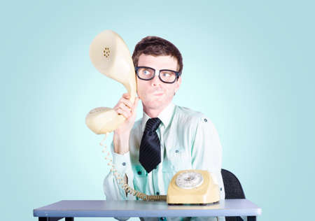 eavesdropper: Picture of a nerd businessman sitting at an office desk holding enlarged telephone receiver to intercept competition intelligence. Market research concept