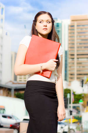 woebegone: Sad Distressed And Devastated Young Business Woman Crying And Sobbing While Walking With Red Folder In Hand In A Sad And Unhappy Business Concept
