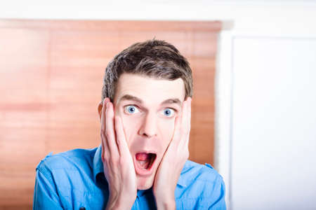 Face of an excited businessman inside work place. Thrill of a business discovery photo