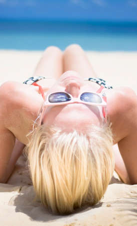 bather: Woman Beach Bather Positions Herself On White Sand At A Topical Island Holiday Destination While Tanning During Summertime In A Summer Sun Beach Bather Image Stock Photo
