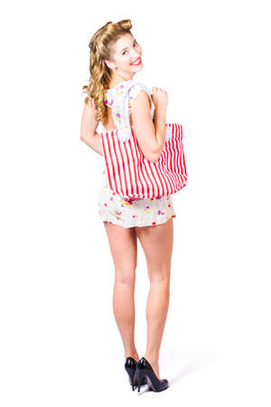 women legs: Isolated full length portrait of a beautiful blond female shopper holding striped shopping bag when buying fashion goods on white background Stock Photo