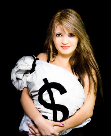 greenbacks: Studio portrait of a happy business woman holding a bag of American dollar bills, in a business success conceptual isolated on black background