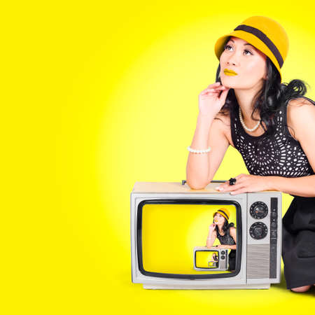50s fashion: Photo of a beautiful vogue girl striking a pose on a vintage tv set in 50s fashion style on yellow background Stock Photo