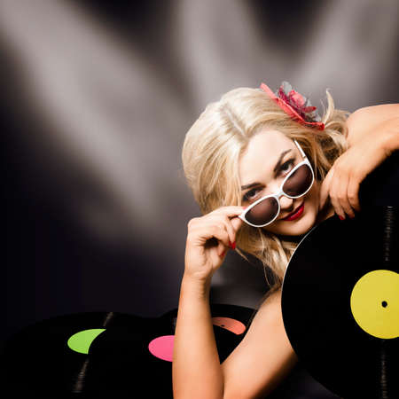 record: Artistic pinup portrait of a female music turntable DJ holding vinyl record under disco stage lights in an audio depiction of retro revival Stock Photo