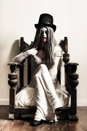 Scary horror image of a spooky elegant fashionable vampire woman in top hat and white dress sitting in a vintage armchair with bloody mouth