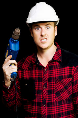 exasperation: Furious out of control construction site worker snarling in fury as he threateningly raises his handheld power drill above his shoulder