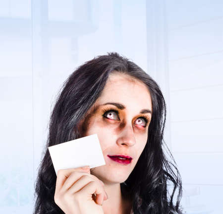 reanimated: Face of a crazy zombie lady thinking with business card to head in a modern office depiction of unhealthy branding Stock Photo