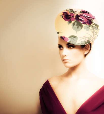 mujer bonita: Retrato artístico entonado de una mujer en la alta moda que llevaba un escote y el sombrero pastillero floral Foto de archivo