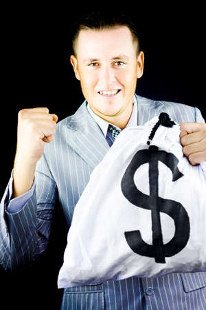 takings: Successful young man in stylish grey suit raising his fist in jubilation at his latest windfall and wealth as shown by the large money bag full of dollars that he is gleefully clutching in his hand