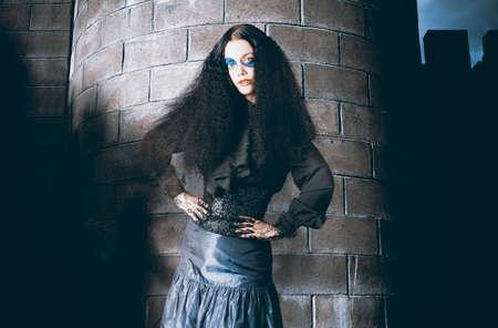 edad media: Femenino Edad Media animador de pie con las manos en las caderas junto a la torre de la fortaleza en traje antiguo de la moda