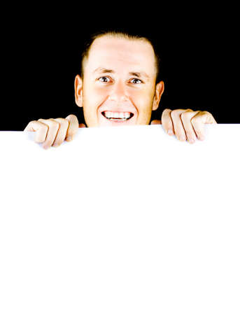 ebullient: Smiling young man holding a blank poster board with space for your message or text