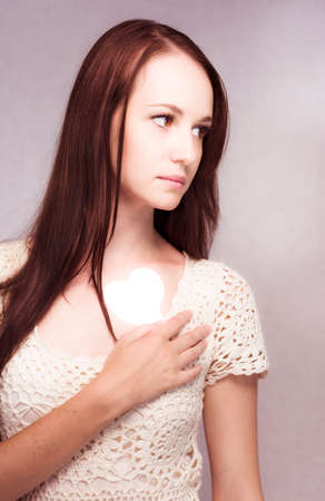 heartbreak issues: Sad young girl holds a white heart to her chest in a concept of love and loss. Stock Photo