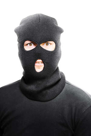 desperation: Wild eyed masked bandit concealed under a black textile mask looking in desperation at the camera as he realises that he has been caught in the act Stock Photo