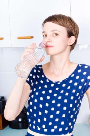 agua potable: Mujer joven morena de beber de una botella de agua mineral en el interior de la cocina moderna Foto de archivo