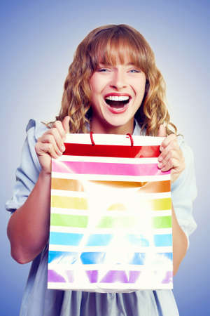 low prices: Bargain shopping woman laughing with joy as she holds up a colourful striped carrier bag with purchases that she has procured at low prices with huge savings