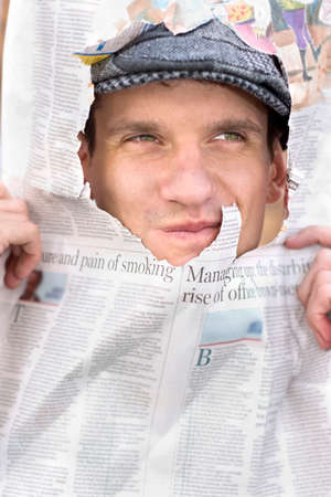 broadsheet: Smiling Young Man In Flat Cap Is Breaking News Headlines By Looking Through A Torn Broadsheet Newspaper Article.