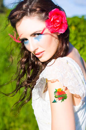 tatt: Wind Blows In The Hair Of A Beautiful Brunette Woman Standing Outside In A Lush Green Meadow With A Love Tattoo On Her Shoulder In A Romantic Symbol
