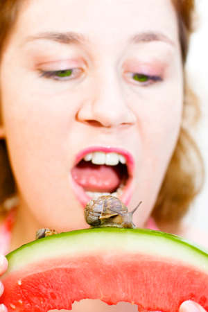 intrude: Lady Opens Her Mouth Wide To Eat The Invading Snails Sliding On The Skin Of Her Sliced Watermelon