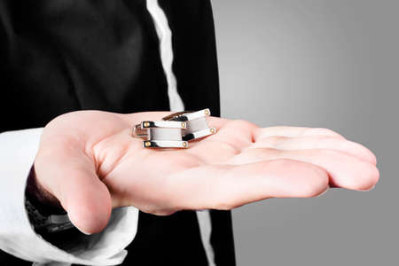 cuff links: Photograph of a male model showcasing premium style cuff links in his hand