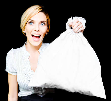 exhilarated: Elated vivacious retail sales woman giving her endorsement holds up a blank white bag suitable for your conceptual text as a moneybag, product or promotional advertising