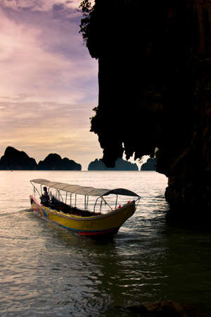 phi phi island: Dusk Sun Set Sees A Boat Mooring Into The Shore Of Thailand During A Tropical Holiday In Asia